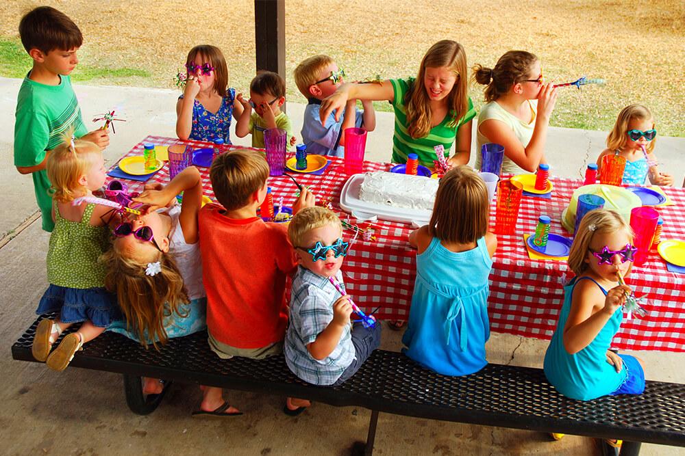 kids enjoying birthday cake at picnic table